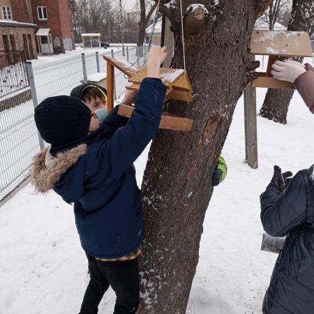 dzieci dokarmiają ptaki